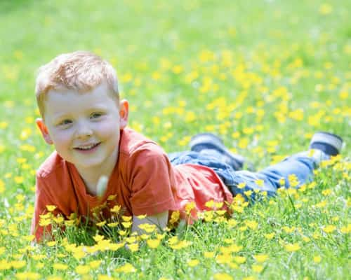 portrait photo of a young boy in a meadow