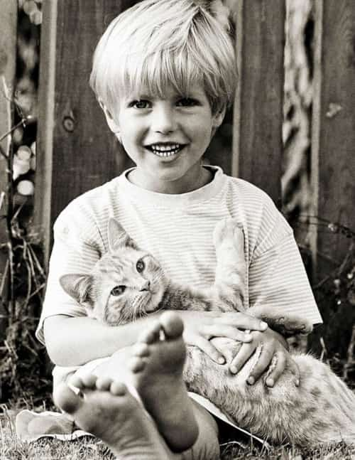 monochrome photo of boy holding a cat
