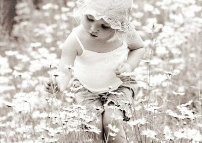 monochrome photo of toddler picking a flower in a meadow