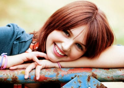 girl with red hair leaning on a gate