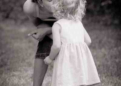 monochrome photo of mother kissing her child in a garden