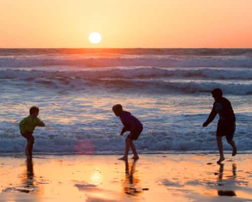 boys playing in the sea at sunset