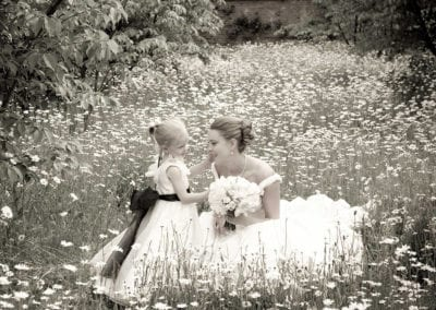 bride and child in field of daisies